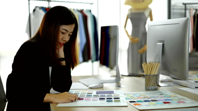 4K Smiling Female Designer Choosing Color For Her Clothes Product In The Office 4K Smiling Female Designer Choosing Color From Color Sample In Color Book At The Office fabric swatch stock videos & royalty-free footage