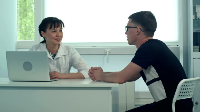 Smiling female doctor listening to male patient in her office video