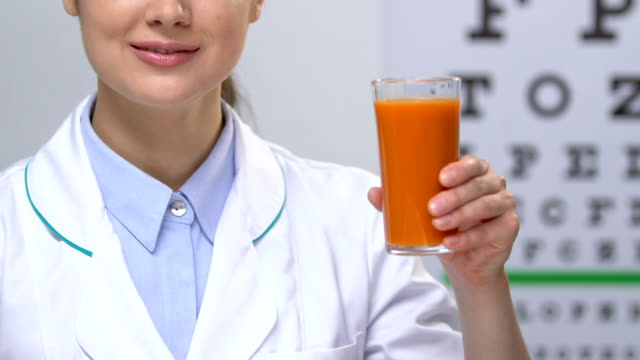Smiling female doctor showing carrot juice against eye chart background, health Smiling female doctor showing carrot juice against eye chart background, health eye chart stock videos & royalty-free footage