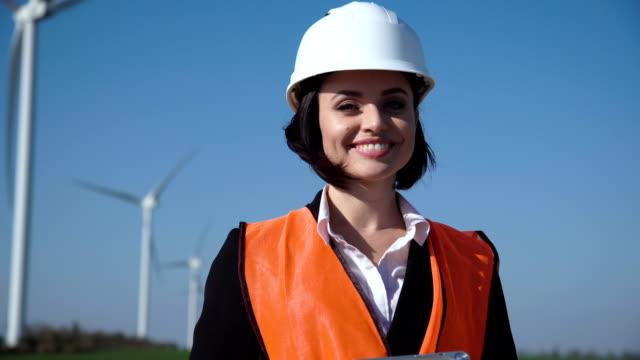 lächelnde ingenieurin gegen windpark - bauarbeiterhelm stock-videos und b-roll-filmmaterial