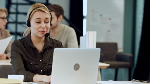 ofiste onun masasında kulaklıklarla gülümseyen kadın yardım hattı operatörü - kesit stok videoları ve detay görüntü çekimi