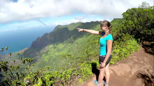 Souriant randonneuse de montagne vue et pointant vers l'océan - Vidéo