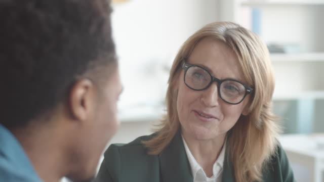 lächelnde weibliche personalmanagerin im gespräch mit young afro-american associate in office - feedback stock-videos und b-roll-filmmaterial