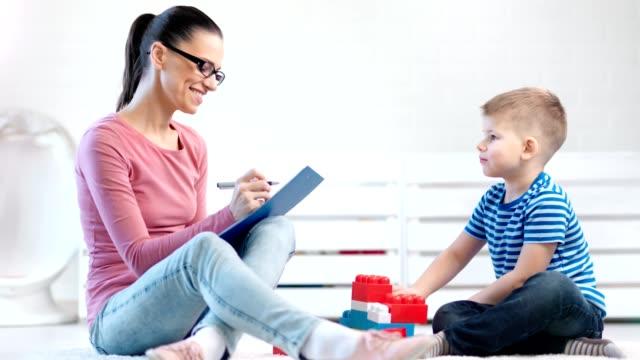 vídeos y material grabado en eventos de stock de psicóloga niña sonriente observando y tomando notas durante las pruebas de psicología - profesional de salud mental