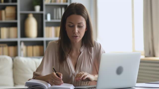 Smiling female online tutor wear earphone speaking teaching web class