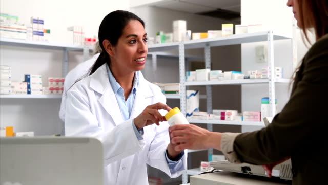 vidéos et rushes de souriant femelle pharmacien donner des médicaments à un client - pharmacie