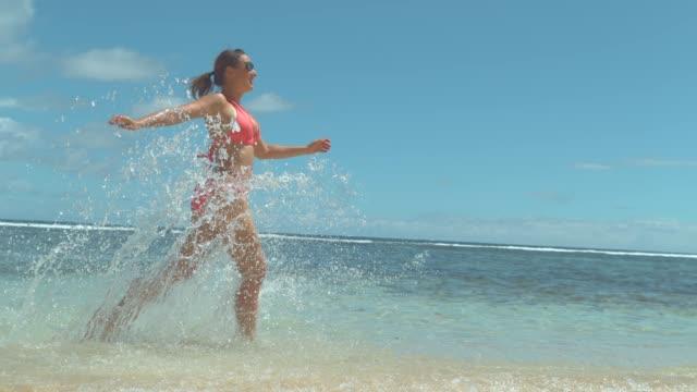 slow motion: gülümseyen kadın plaj çalış ve deniz suyu her yerde su sıçramalarına - sadece genç bir kadın stok videoları ve detay görüntü çekimi