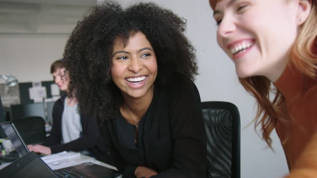 Smiling female professionals working together at office. Two smiling female professionals working together at office with a male colleague. Businesswomen discussing work and smiling at office. software developer stock videos & royalty-free footage