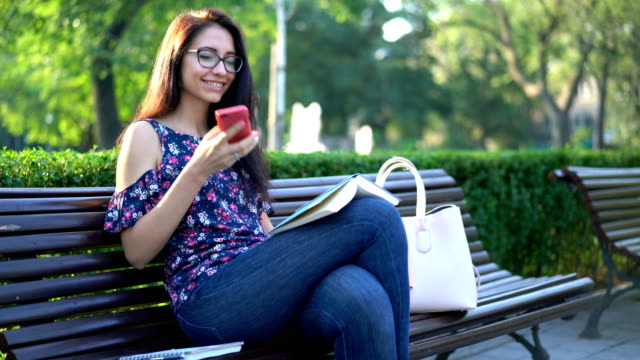 smiling female reading a book and answering her phone - садовая скамья стоковые видео и кадры b-roll