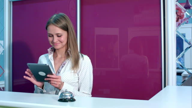 Smiling female receptionist with tablet welcoming hotel guests video