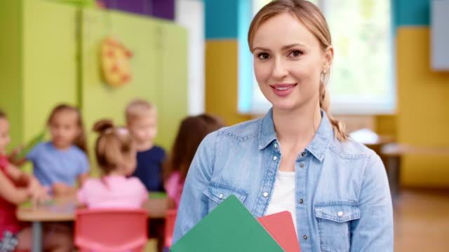 stockvideo's en b-roll-footage met lachende vrouwelijke leraar in de voorschoolse - peuterklasleeftijd
