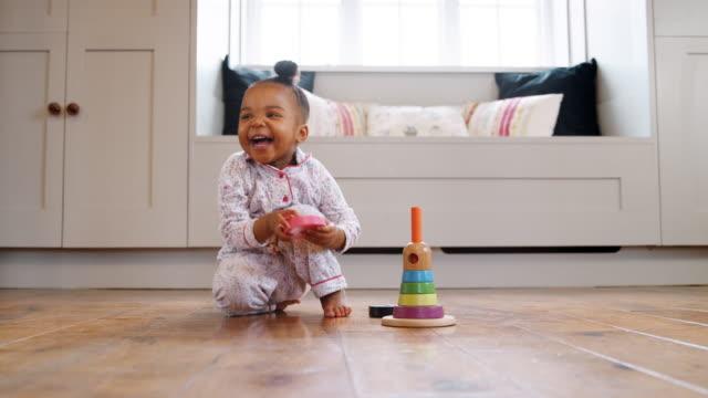 stockvideo's en b-roll-footage met lachende vrouw peuter thuis spelen met houten stapelen speelgoed - baby toy