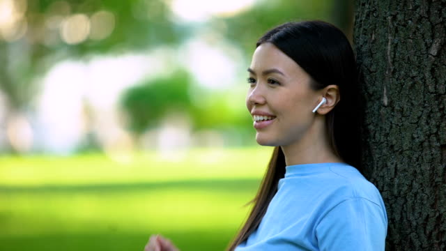 donna sorridente che indossa auricolari wireless che ascolta musica seduta nel parco - auricolari wireless video stock e b–roll