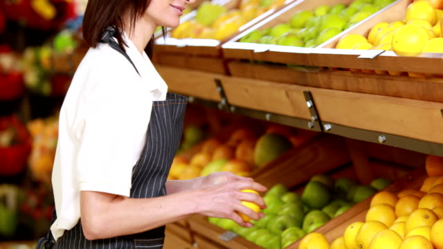 Smiling female worker stocking lemons Portrait of smiling female worker stocking lemons in grocery store christmas stocking stock videos & royalty-free footage