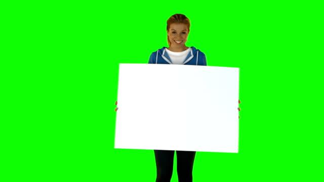 улыбающаяся fit блондинка, показывая плакат - poster стоковые видео и кадры b-roll