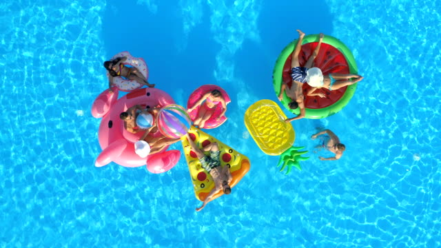 AERIAL: Smiling fit people playing with a ball on fun colourful floaties in pool AERIAL TOP DOWN: Happy girls and guys playing with ball on floaties in pool. Cheerful smiling friends enjoying summer vacation on inflatable pineapple, pizza, flamingo, watermelon and doughnut floats volleyball sport stock videos & royalty-free footage