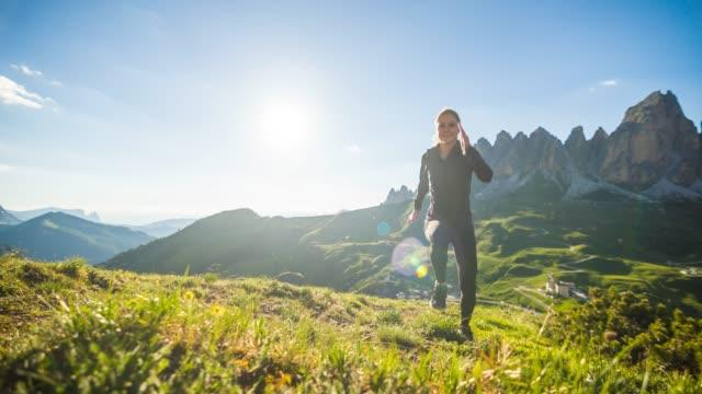 leende passa kvinnan kör uppför en gräsbevuxen stig på en äng i fjällterräng - jogging hill bildbanksvideor och videomaterial från bakom kulisserna