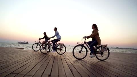 amici sorridenti in bicicletta in mare - abbigliamento casual video stock e b–roll
