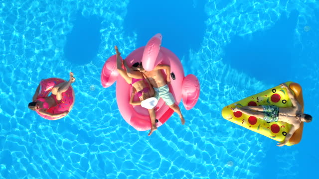 AERIAL: Smiling friends enjoying summer vacation on pizza, doughnut and flamingo video
