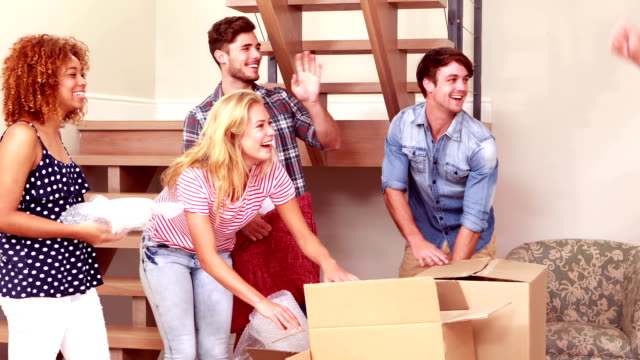 Smiling friends moving boxes together while saying goodbye video
