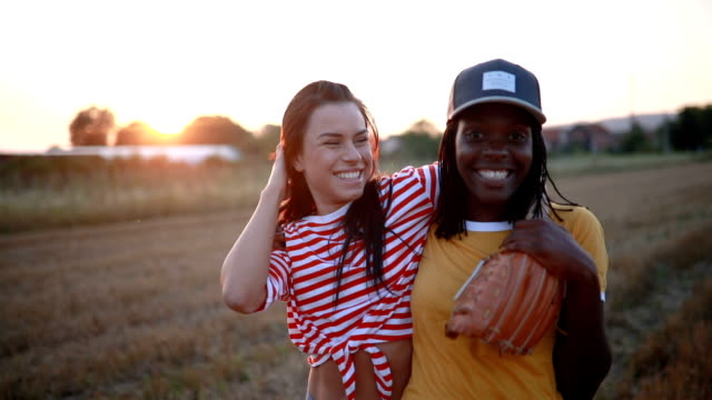 Smiling friends playing baseball outdoors video