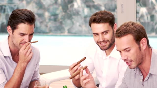 sorridendo gli amici di fumare sigari in soggiorno - sigaro video stock e b–roll