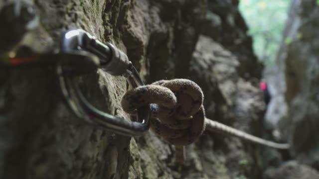 stockvideo's en b-roll-footage met glimlachende meisje alpinist klimt een touw in de bergen en benaderingen van de camera - touw