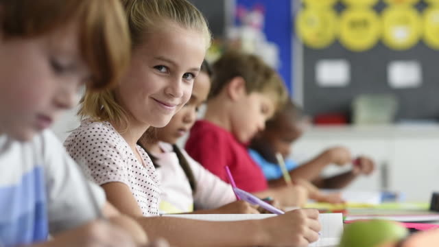Smiling girl doing classwork Happy beautiful schoolgirl doing classwork while looking at camera. Smiling scholar girl sitting at school desk with her classmates in background. Young pretty kid enjoying study in elementary school. elementary age stock videos & royalty-free footage