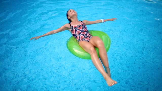 Smiling girl enjoying floating at the pool Cute and gorgeous young woman enjoying her leisure summer time at the outdoor pool. standing water stock videos & royalty-free footage