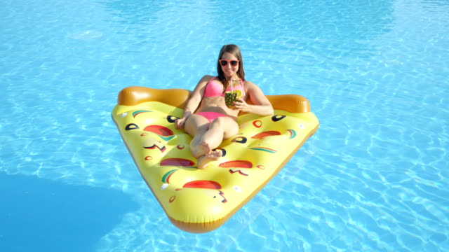 CLOSE UP: Smiling girl enjoying summer vacation on inflatable pizza floatie video