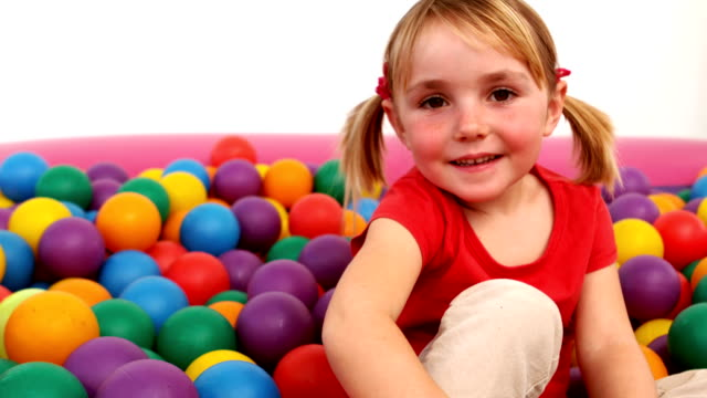 Smiling girl inside a ball pit video