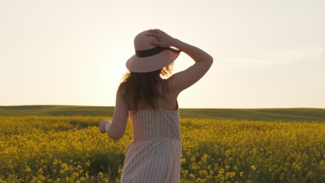 ein lächelndes mädchen rennt über das feld und hält ihren hut. feld mit gelben blüten. sonnenuntergang im hintergrund. 4k - kopfbedeckung stock-videos und b-roll-filmmaterial
