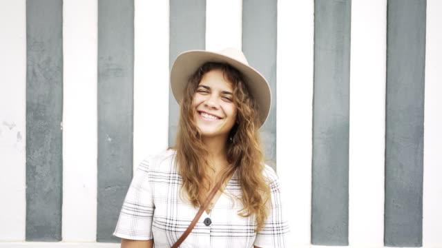 vídeos de stock e filmes b-roll de smiling girl leaning on colorful house wall - aveiro