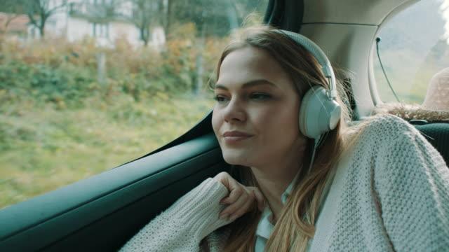 smiling girl listening music on back seat of the car - cuffia attrezzatura per l'informazione video stock e b–roll