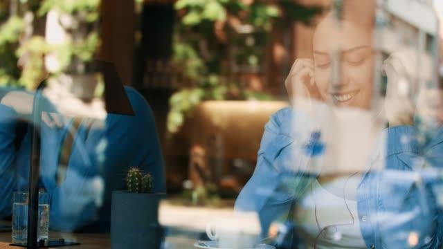 vídeos de stock e filmes b-roll de smiling girl looking through the window - bar local de entretenimento
