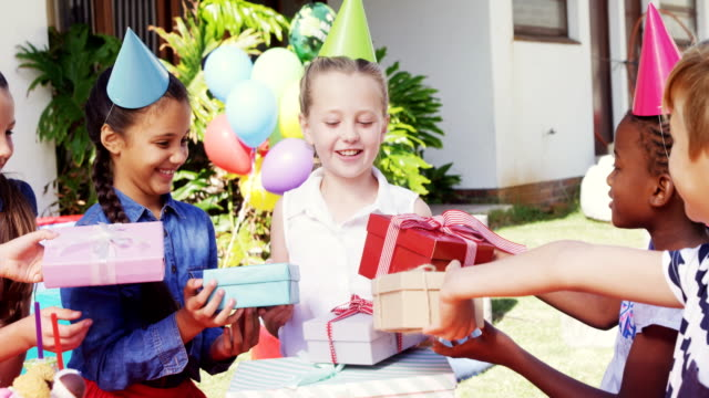 Smiling girl receiving gifts from friends 4k video