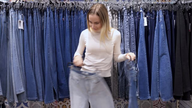 Smiling girl shopper choosing new jeans at store Smiling girl shopper choosing new jeans at store. choice stock videos & royalty-free footage
