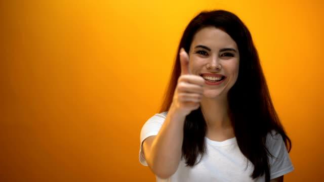 smiling girl showing thumbs up, satisfied client likes service, good feedback - brązowe włosy filmów i materiałów b-roll