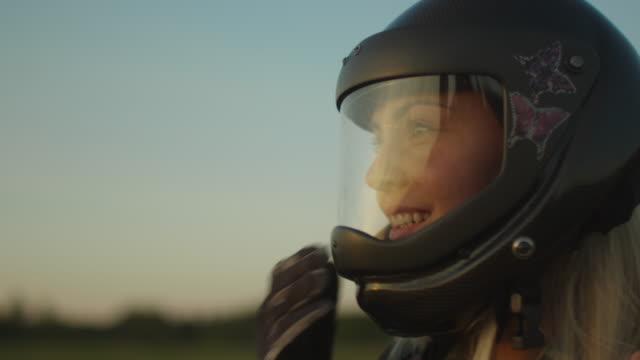 vídeos de stock, filmes e b-roll de sorrindo a garota para-quedista é tirar o capacete após a aterragem bem sucedida - paraquedismo