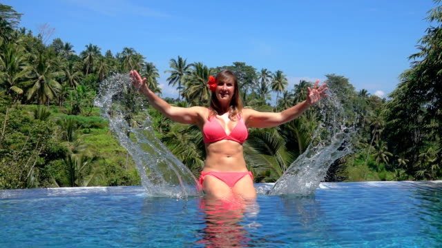 vídeos de stock e filmes b-roll de close up smiling girl splashing waterdrops in infinity pool on tropical island - mulher natureza flores e piscina