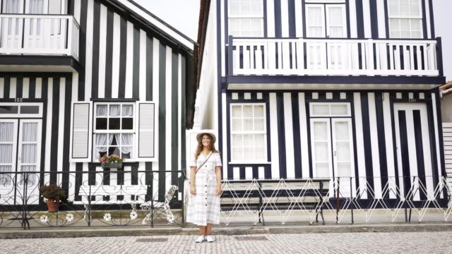 vídeos de stock e filmes b-roll de smiling girl standing near pretty houses - aveiro