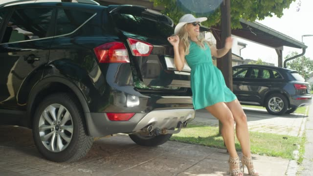 LENS FLARE: Smiling girl tries to close the trunk of her car stuffed with bags. SLOW MOTION, LENS FLARE: Smiling Caucasian girl tries to close the trunk of her big black car stuffed with heavy travel bags. Cheerful young woman in green sundress struggles with packing her luggage. stuffed stock videos & royalty-free footage
