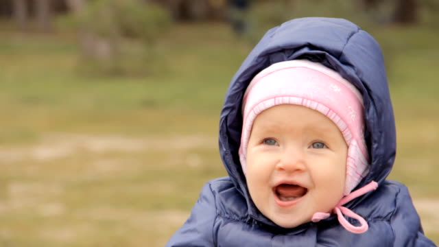 A smiling girl wearing a cap and a jacket with the hood on video