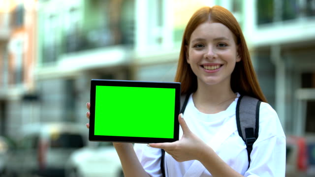 Smiling girl with backpack showing green screen tablet, cheap tours and flights