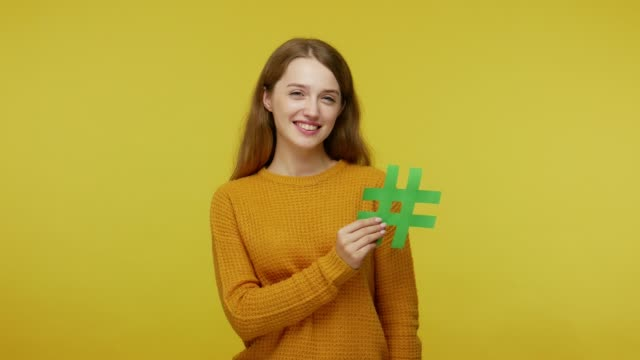 smiling girl with friendly kind face expression holding green hash sign and raising palm to show copy space, - верующий стоковые видео и кадры b-roll