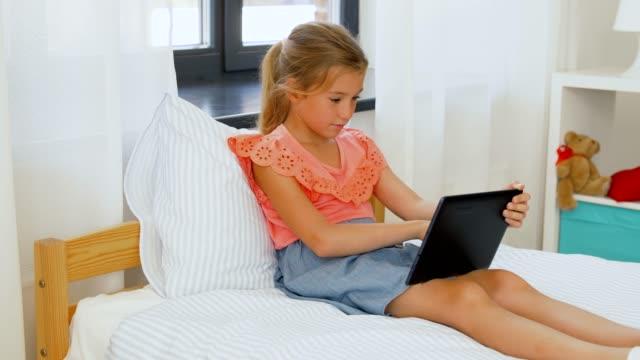 leende flicka med tablet pc sitter på sängen hemma - endast flickor bildbanksvideor och videomaterial från bakom kulisserna