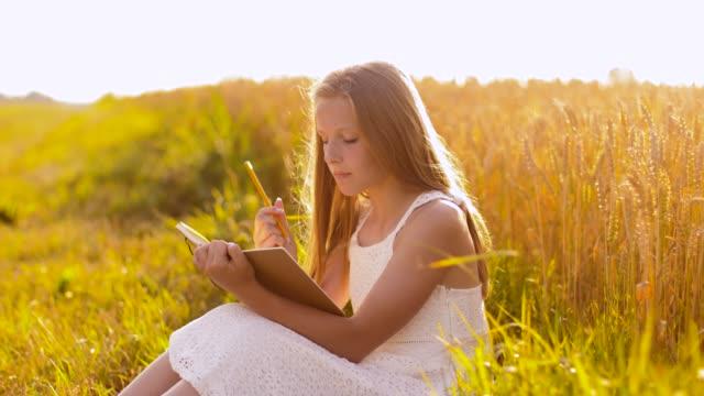 leende flicka skriver till dagbok på spannmål fält video