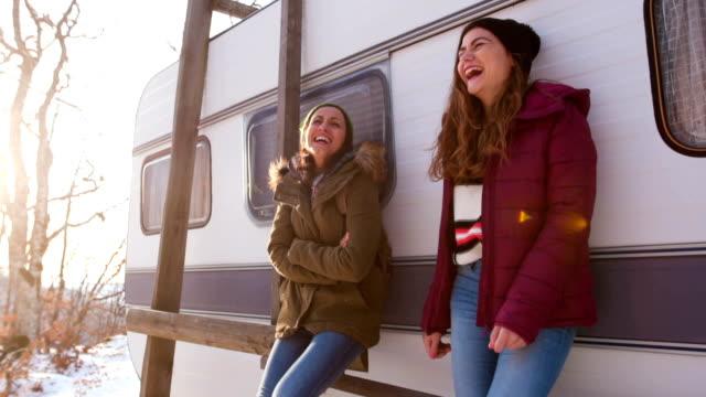 stockvideo's en b-roll-footage met glimlachend vriendinnen voor een vintage camper aanhangwagen - caravan