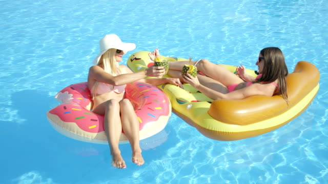 Smiling girls relaxing on inflatable doughnut and pizza, sipping cocktail drinks video