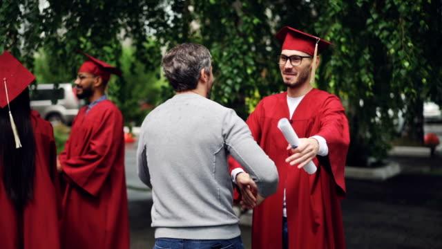vídeos de stock, filmes e b-roll de estudante de graduação sorridente é apertar a mão de seu pai e abraçando-o, jovem em copos é usando chapéu e vestido e detentor de diploma. conceito de educação e sucesso. - beca